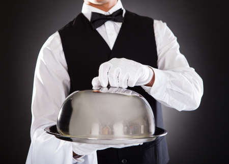 Portrait Of A Male Waiter Holding Tray And Lid Over Black Background