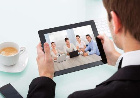 Photo pour Close-up Of Businessman Looking At Video Conference On Digital Tablet - image libre de droit