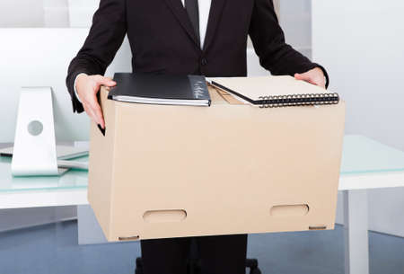 Close-up Of A Businessman Carrying Box At His Workplace
