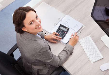 Portrait Of Smiling Young Female Accountant Calculating Bills