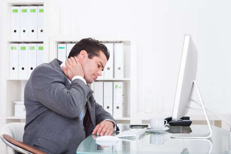 Young Businessman In Office At Desk Suffering From Neck Pain