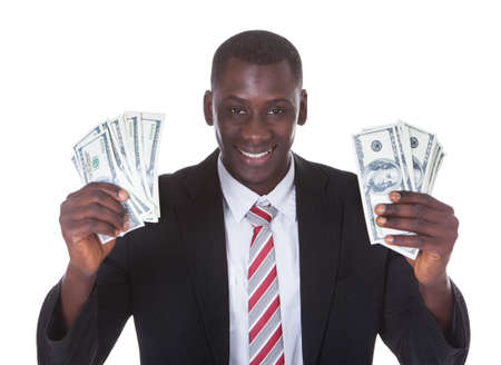 Portrait Of Young Businessman Holding Banknotes Over White Background