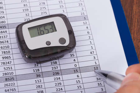 Close-up Of Hand Holding Pen Over Sheet With Digital Pedometer