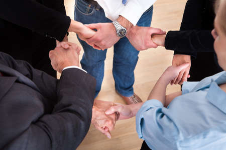 Photo pour High Angle View Of Businesspeople Holding Hands - image libre de droit