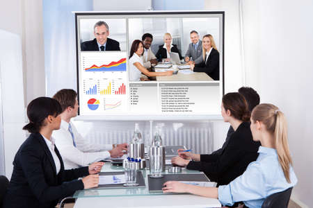 Photo pour Businesspeople Sitting In A Conference Room Looking At Screen - image libre de droit