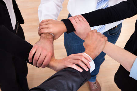 Photo pour High Angle View Of Businesspeople Holding Wrist - image libre de droit