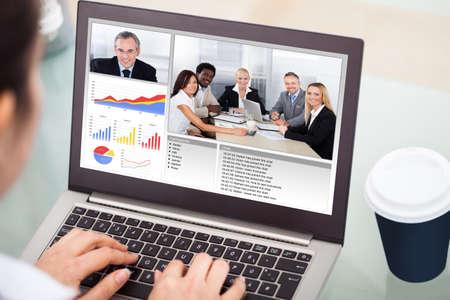 Photo pour Close-up Of Businesswoman Video Conferencing On Laptop With Disposable Cup - image libre de droit