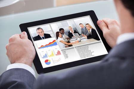 Photo pour Close-up Of Businessman Video Conferencing With Co-worker About Progress Chart - image libre de droit
