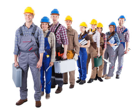 Large group of construction workers or workmen and women queuing up in a long line carrying their tool kits as they wait to clock in or be hired for a job  isolated on white