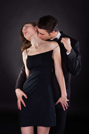 Young man in suit kissing woman on neck while removing dress strap from her shoulder isolated over black background