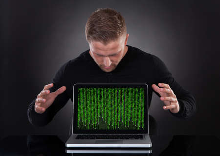 Man or hacker stealing data from a laptop at night bending forwards over the keyboard in the glow from the screen as he browses the internet or retrieves and downloads personal data