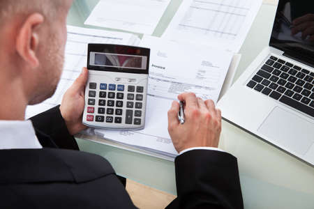 High angle over the shoulder view of a businessman checking figures in a report looking down onto the calculator and paperwork