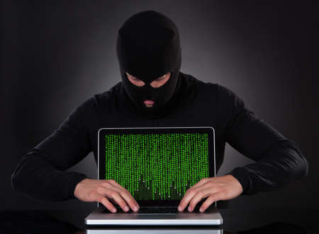 Hacker in a balaclava standing in the darkness furtively stealing data off a laptop computer or inserting spyware in an online security and risk concept
