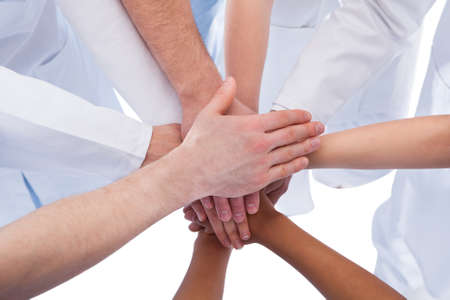 Photo pour Doctors and nurses stacking hands. Isolated on white - image libre de droit