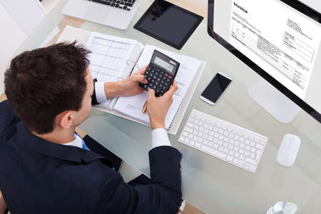 High angle view of businessman calculating tax at desk in office