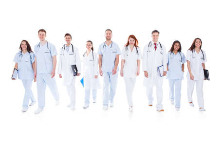 Large diverse group of doctors and nurses in uniform walking towards camera isolated on white