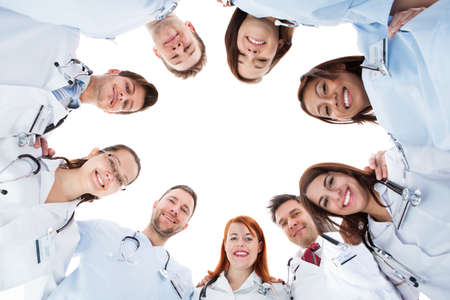 Photo pour Large diverse multiethnic medical team standing grouped in a circle all looking down at the camera and smiling isolated on white with central copyspace - image libre de droit