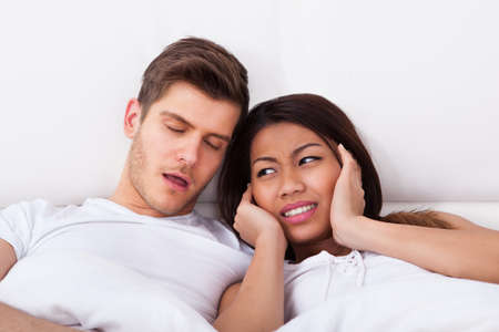 Irritated young woman covering ears while looking at snoring man in bed at home