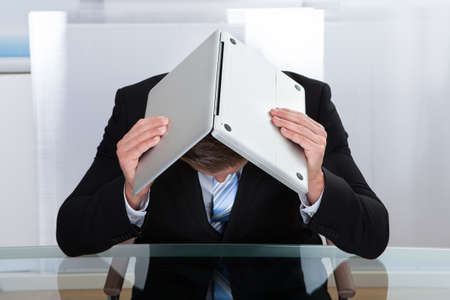 Depressed businessman sitting at a reflective table hiding under his laptop as he holds it open over his bowed head