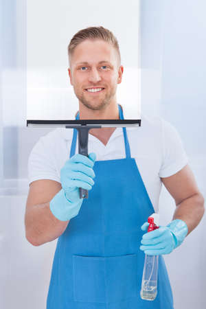 Male janitor using a squeegee to clean a window in an office wearing an apron and gloves as he works