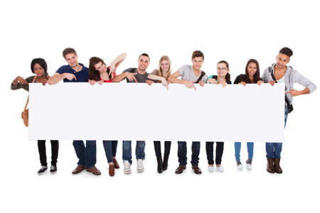 Photo pour Full length portrait of confident multiethnic college students displaying blank billboard against white background - image libre de droit