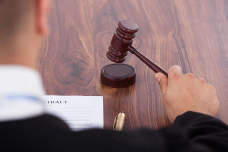 Cropped image of judge knocking gavel in courtroom