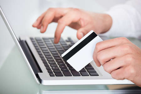 Cropped image of man shopping with credit card and laptop