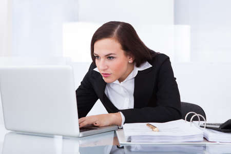 Concentrated young businesswoman using laptop at desk in office