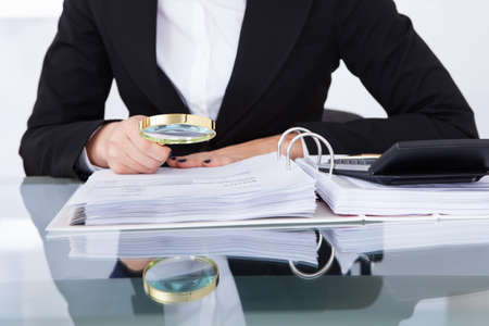 Closeup of uditor scrutinizing financial documents at desk in office