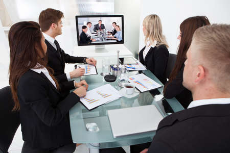 Photo pour Businesspeople attending video conference at desk in office - image libre de droit