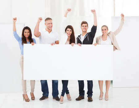 Full length portrait of confident businesspeople holding blank billboard in office