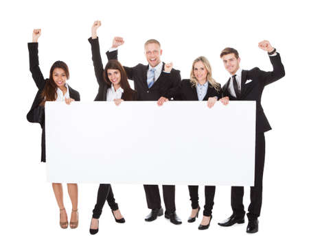 Full length portrait of confident businesspeople holding blank banner against white background