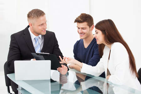 Smiling young couple discussing with financial advisor at office desk