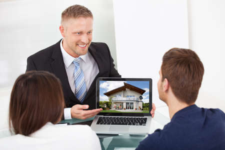 Smiling advisor showing house picture to couple on laptop at office desk