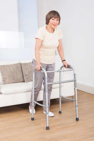 Full length portrait of senior woman using walking frame at nursing home