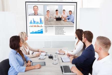 Photo pour Business team attending video conference at desk in office - image libre de droit