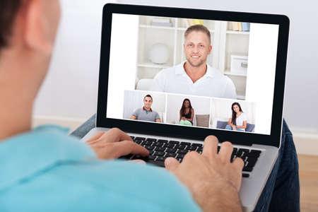 Photo pour Man having video conference with friends on laptop at home - image libre de droit