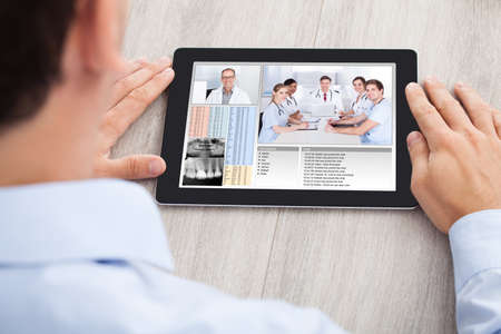 Photo pour Cropped image of businessman video conferencing with medical team on digital tablet at desk in office - image libre de droit