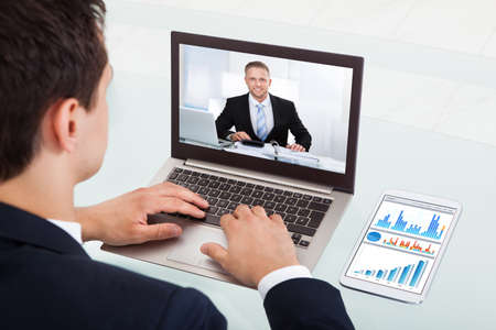 Photo pour Cropped image of young businessman video conferencing on laptop at desk in office - image libre de droit