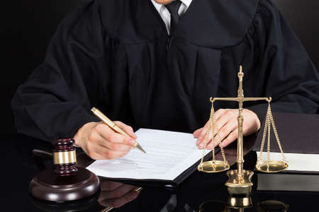 Midsection of male judge writing on paper at desk against black background