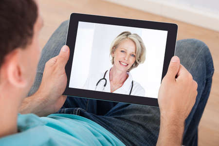 Man having video chat with female doctor on digital tablet at homeの写真素材
