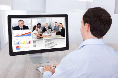 Photo pour Rear view of businessman video conferencing with colleagues on desktop PC at office desk - image libre de droit