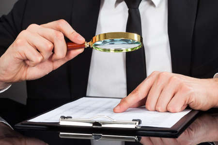 Midsection of young businessman analyzing document with magnifying glass at desk