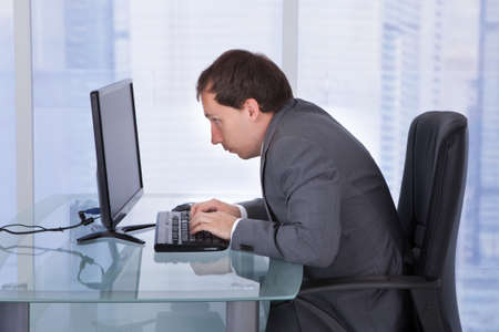 Photo pour Side view of concentrated businessman working on computer at desk in office - image libre de droit