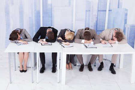 Photo for Group of tired corporate personnel officers sleeping at table in office - Royalty Free Image