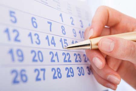 Photo pour Closeup of woman's hand marking date 15 on calendar - image libre de droit