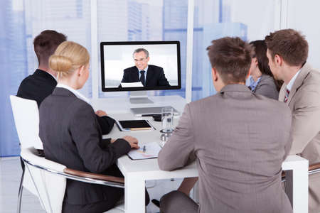 Photo pour Group of business people in video conference at meeting table - image libre de droit
