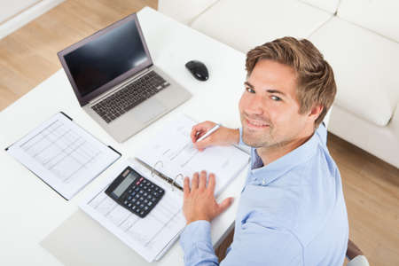 High angle portrait of businessman calculating tax at desk in office