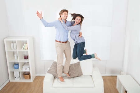 Full length of playful couple jumping on sofa at home