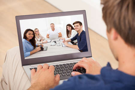 Photo pour Cropped image of man attending conference meeting on laptop at home - image libre de droit